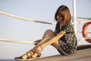siedząca kobiueta dotyka nóg