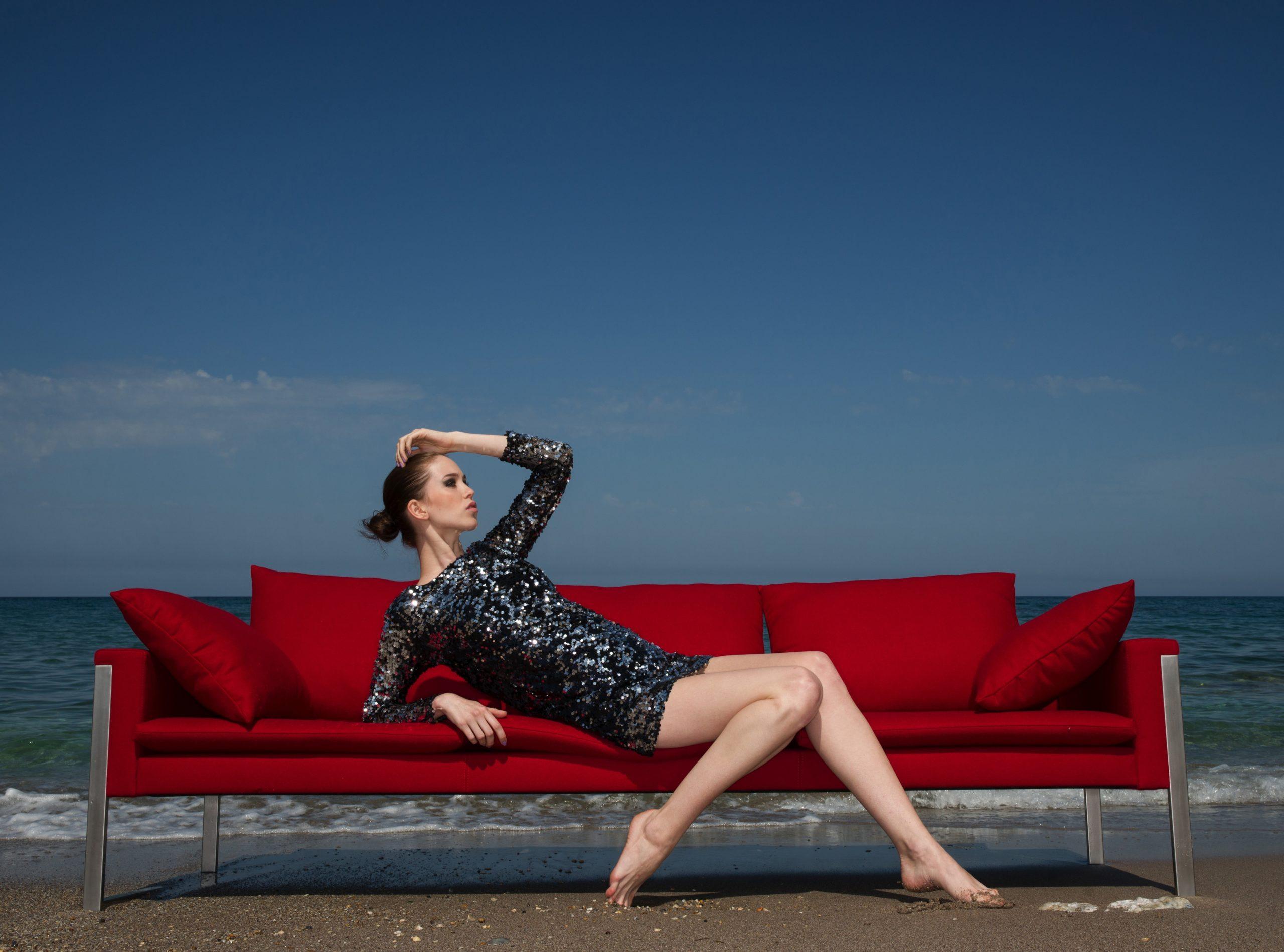 Kobieta siedzi na czarwonej kanapie