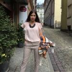 Kobieta w różowej bluzce i szarych spodniach