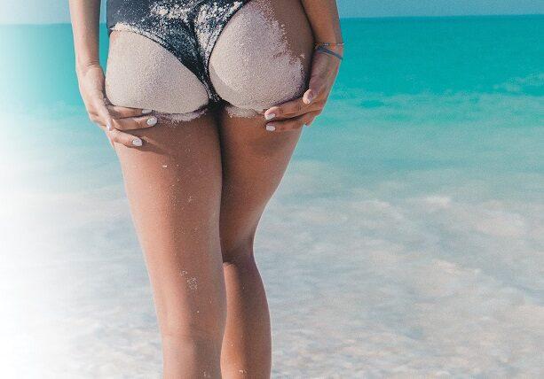 Kobieca pupa oblepiona piaskiem