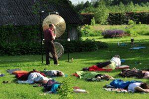ludzie leżą na trawie słuchają gongów