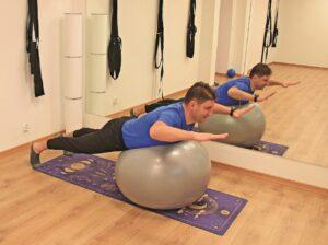 Mężczyzna ćwiczy jogę na piłce